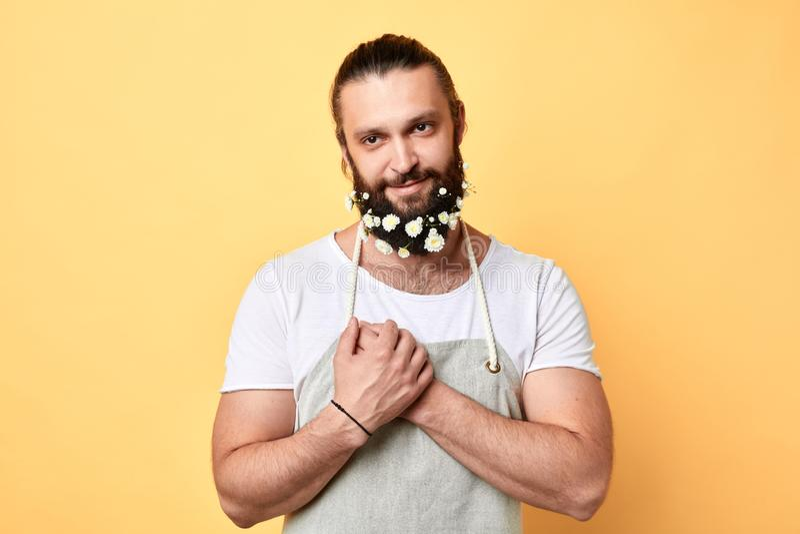 Hombre alegre barbudo atractivo, brutal con las flores en barba imagen de archivo libre de regalías