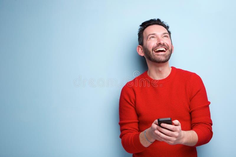 Hombre alegre con el teléfono móvil que mira para arriba imagenes de archivo
