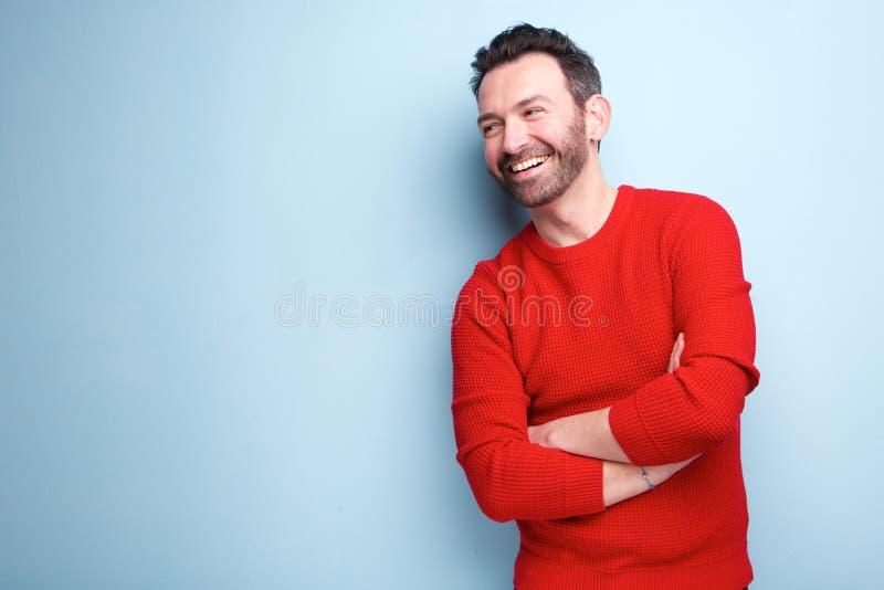 Hombre alegre con la barba que ríe contra fondo azul fotografía de archivo libre de regalías