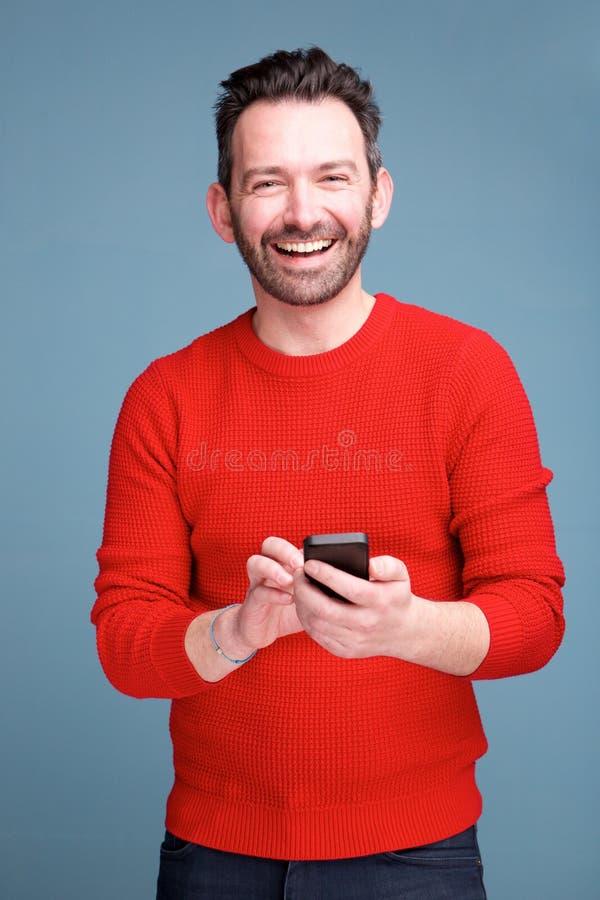 Hombre alegre con la barba que sostiene el teléfono móvil contra fondo azul foto de archivo libre de regalías