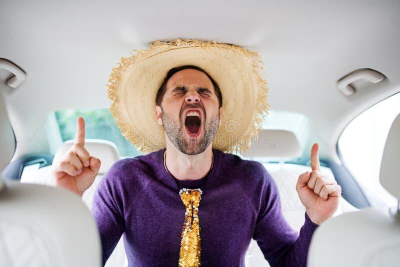 Hombre alegre con los accesorios del partido que se sientan en coche, divirtiéndose imagenes de archivo