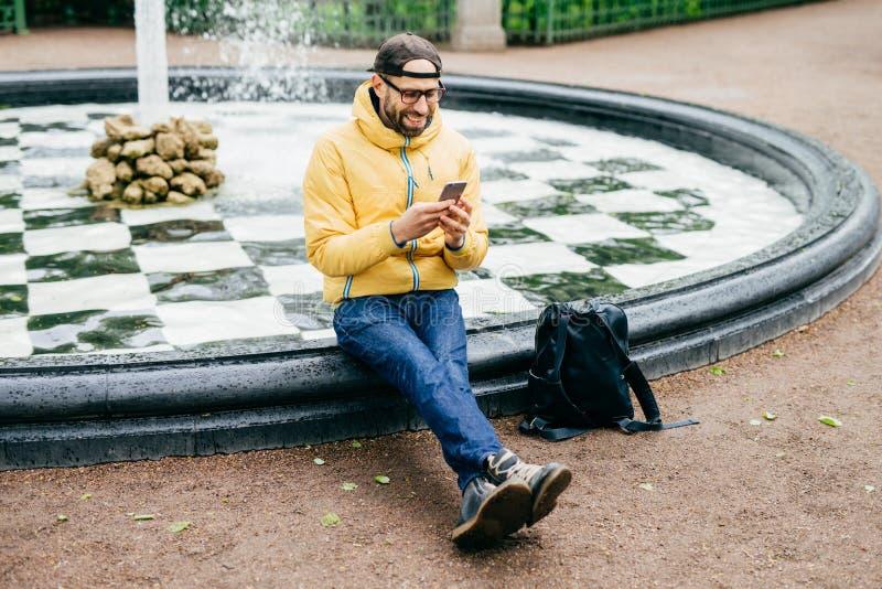 Hombre alegre en el casquillo, las lentes y el anorak amarillo sentándose cerca de la fuente charlando con los amigos que usan el imagen de archivo