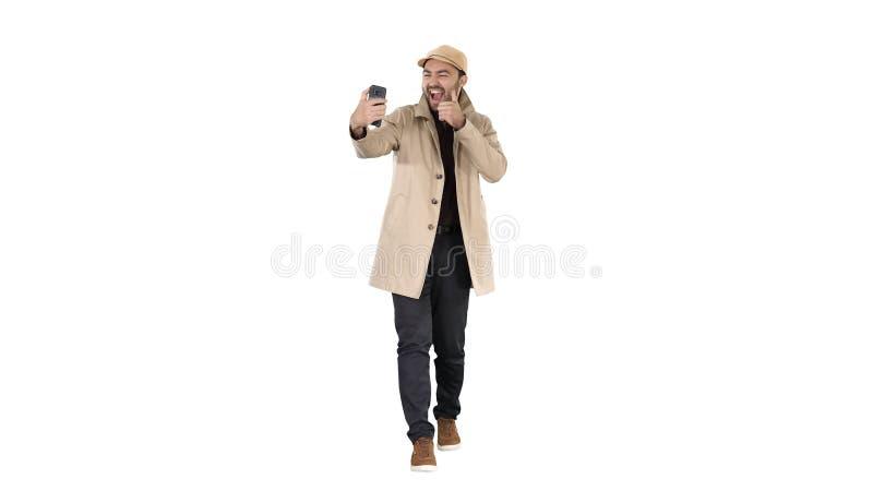 Hombre alegre en la capa que toma la foto que hace el selfie en el fondo blanco imágenes de archivo libres de regalías