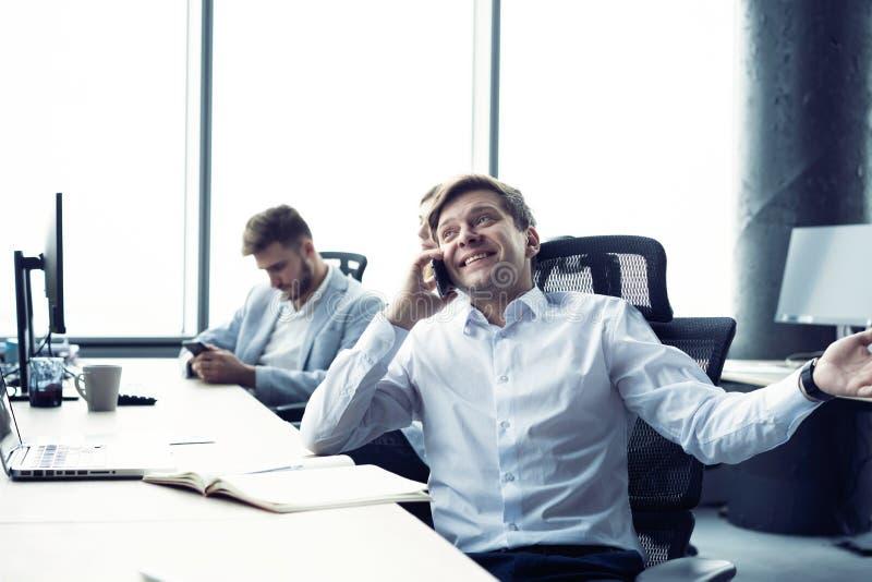 Hombre alegre en la oficina que contesta al tel?fono fotos de archivo libres de regalías