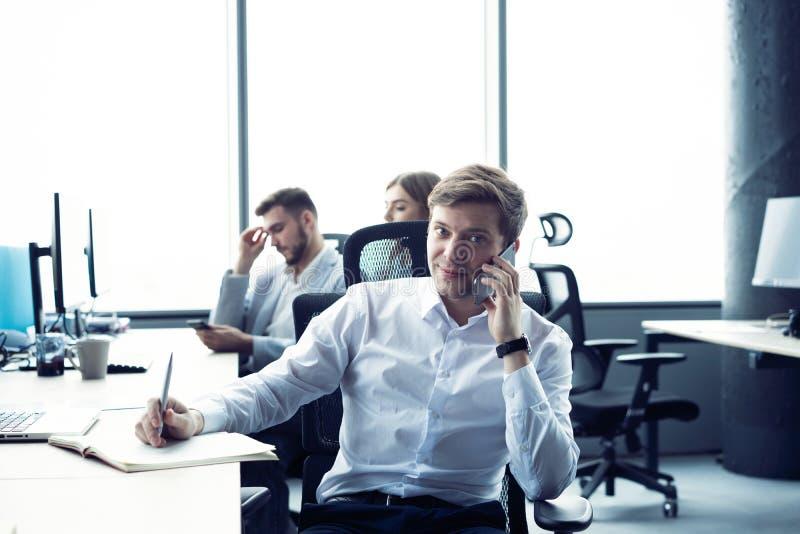 Hombre alegre en la oficina que contesta al tel?fono fotografía de archivo libre de regalías