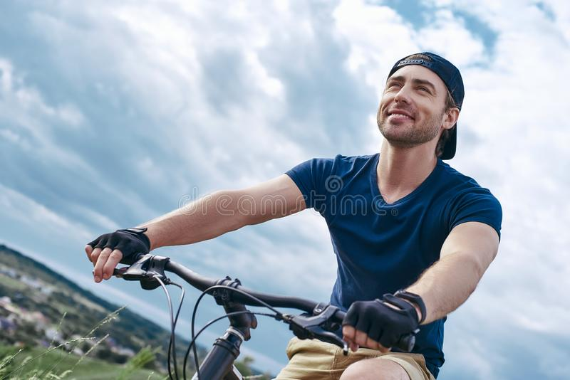 Hombre alegre, en la reconstrucción activa en una bici de montaña imagen de archivo libre de regalías