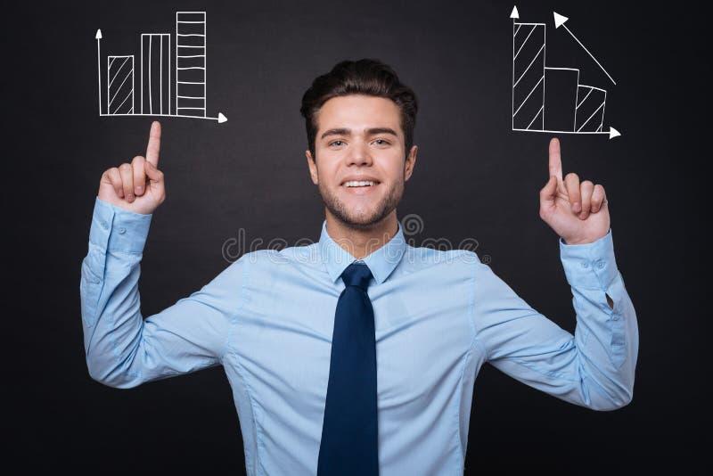 Hombre alegre en la ropa formal que presenta ideas comerciales foto de archivo