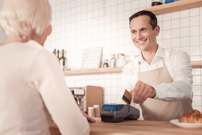 Hombre alegre encantado que usa una tarjeta de crédito imagenes de archivo