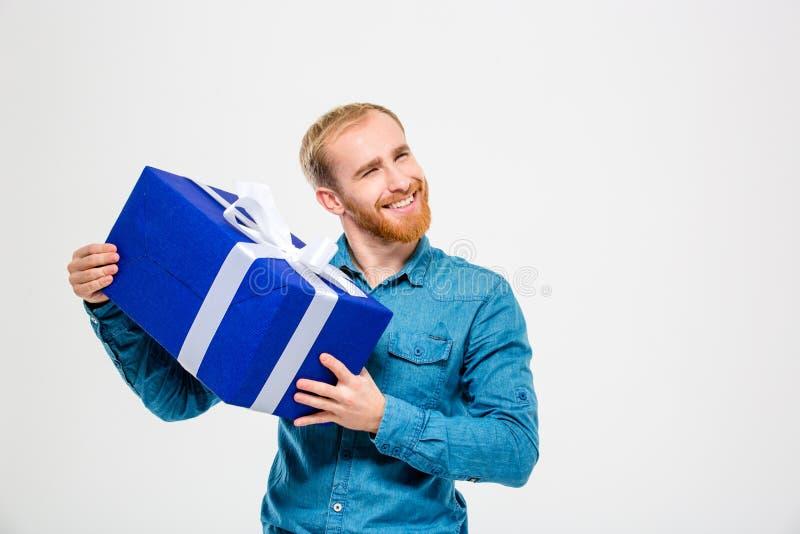 Hombre alegre feliz con la barba que lleva a cabo un presente foto de archivo libre de regalías