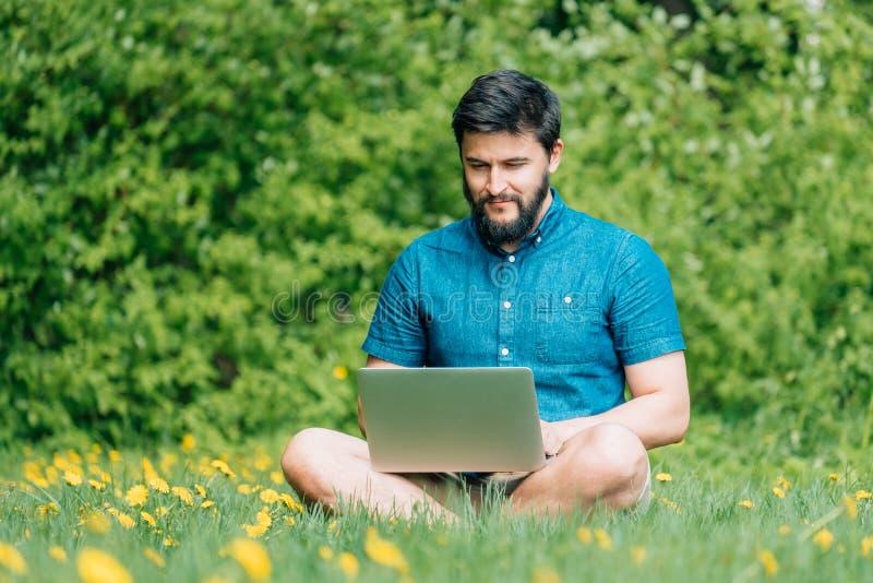 Hombre alegre feliz del inconformista con un ordenador portátil que se sienta al aire libre en gre imágenes de archivo libres de regalías