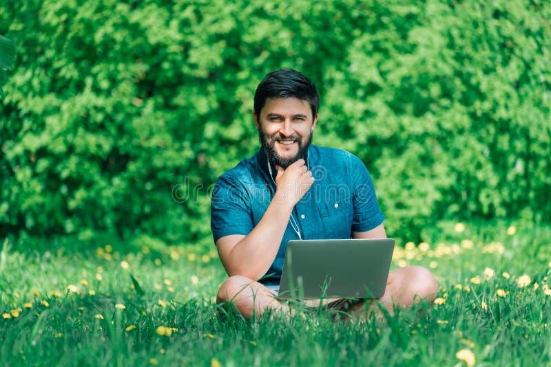 Hombre alegre feliz del inconformista con un ordenador portátil que se sienta al aire libre en gre imagen de archivo