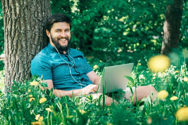 Hombre alegre feliz del inconformista con un ordenador portátil que se sienta al aire libre en gre imagenes de archivo