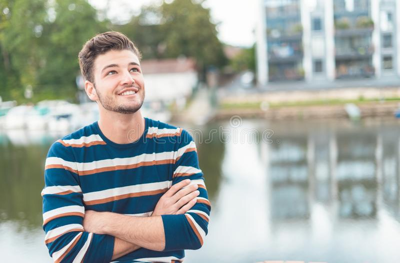 Hombre alegre hermoso de la sonrisa delante del positiv de pensamiento del río imagen de archivo libre de regalías