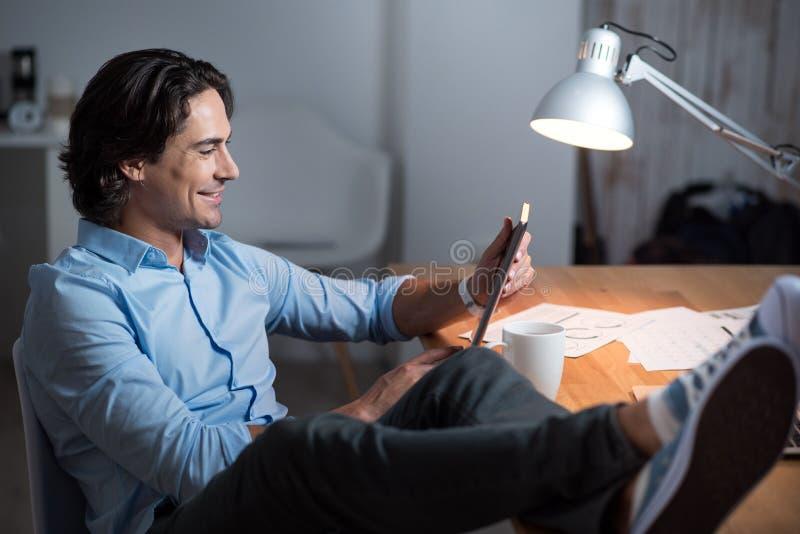 Hombre alegre hermoso de yang que usa la tableta imágenes de archivo libres de regalías