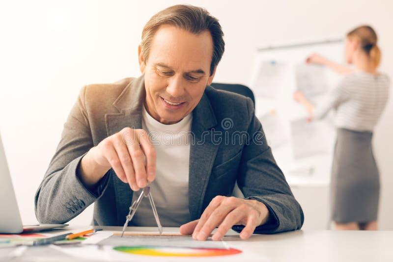 Hombre alegre hermoso que lleva a cabo un par de compases imágenes de archivo libres de regalías