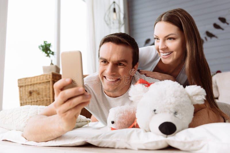 Hombre alegre hermoso que usa su smartphone imagen de archivo