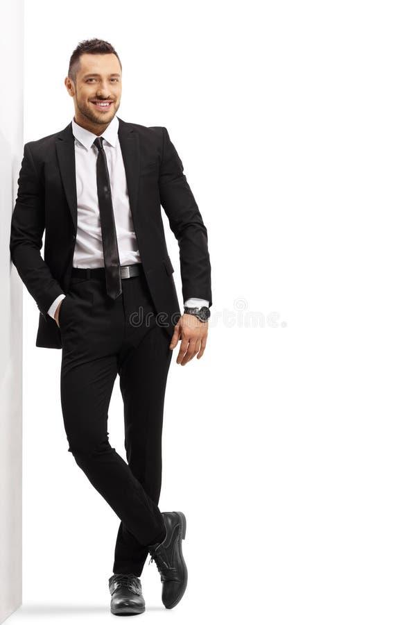 Hombre alegre joven en un traje negro que se inclina en una pared foto de archivo