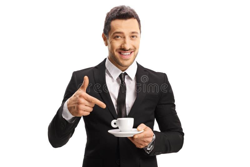 Hombre alegre joven en un traje que sostiene una taza de café y de señalar fotos de archivo