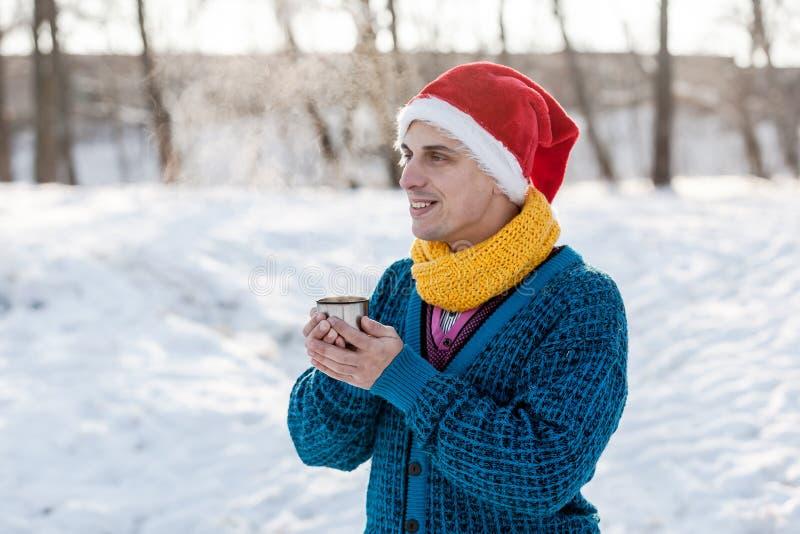 Hombre alegre que bebe té caliente con el vapor al aire libre imagen de archivo