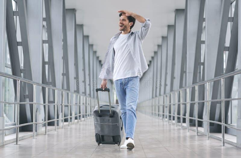 Hombre alegre que camina con equipaje en el aeropuerto fotos de archivo