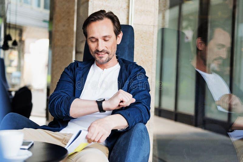 Hombre alegre que comprueba tiempo en el reloj imágenes de archivo libres de regalías