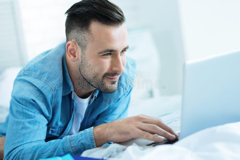 Hombre alegre que disfruta del trabajo en el ordenador portátil foto de archivo libre de regalías
