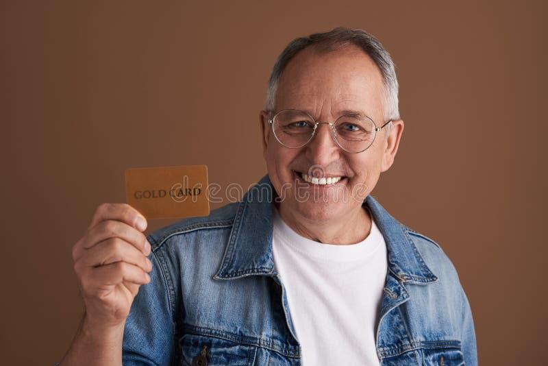 Hombre alegre que es orgulloso de su tarjeta y sonrisa del oro imágenes de archivo libres de regalías