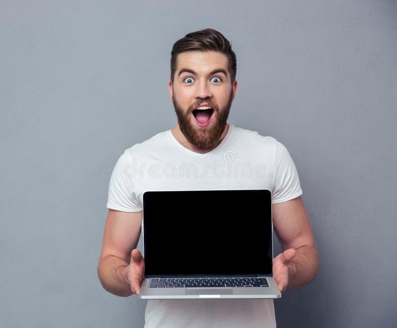 Hombre alegre que muestra la pantalla de ordenador portátil en blanco imagen de archivo