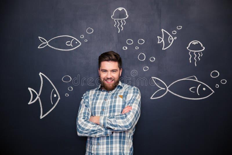 Hombre alegre que se coloca sobre la pizarra con los pescados y las medusas exhaustos foto de archivo libre de regalías
