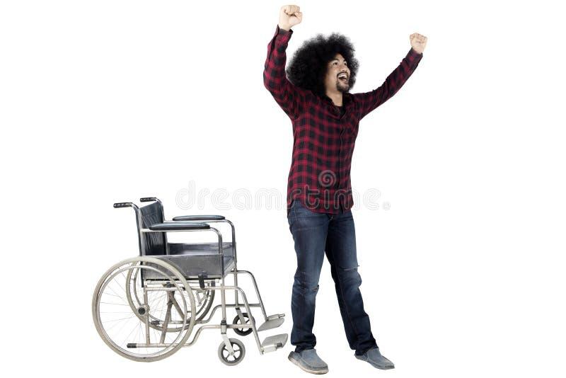 Hombre alegre que se levanta de la silla de ruedas fotos de archivo