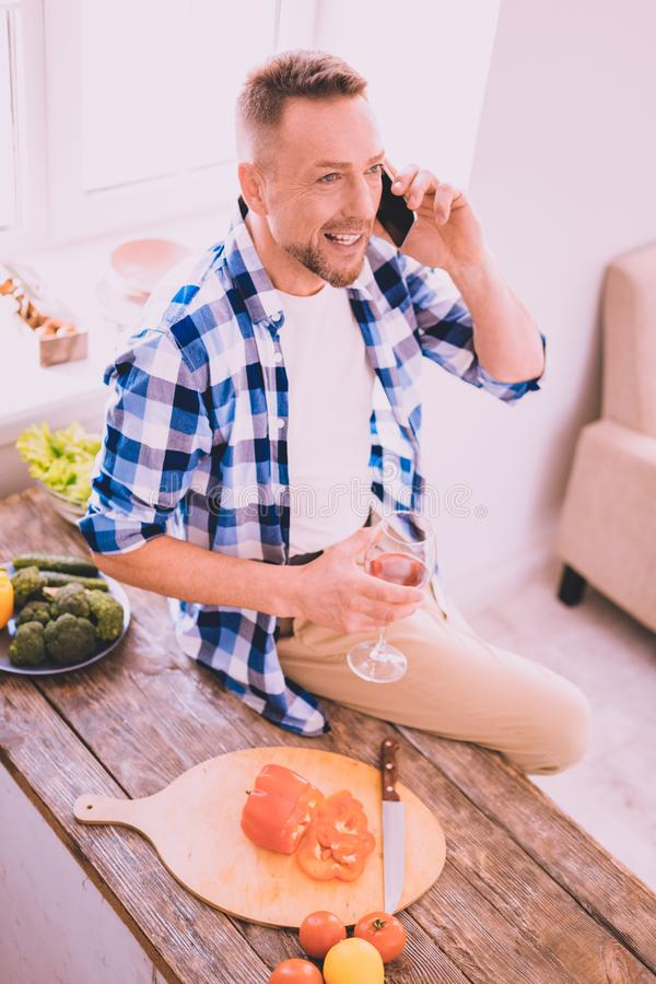 Hombre alegre que tiene una conversación con un amigo en el teléfono imágenes de archivo libres de regalías