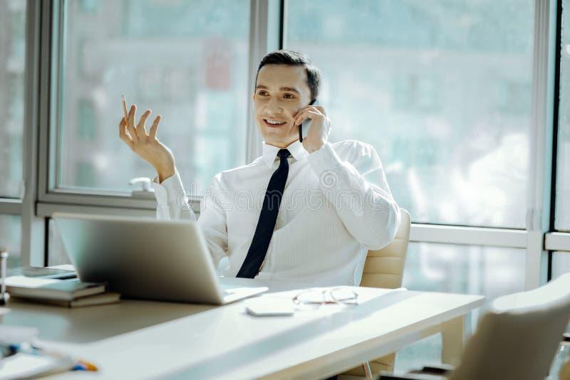 Hombre alegre que tiene una conversación telefónica agradable en oficina foto de archivo libre de regalías
