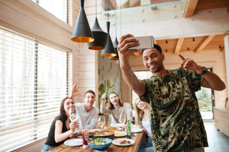Hombre alegre que toma el selfie con sus amigos en la tabla fotos de archivo libres de regalías