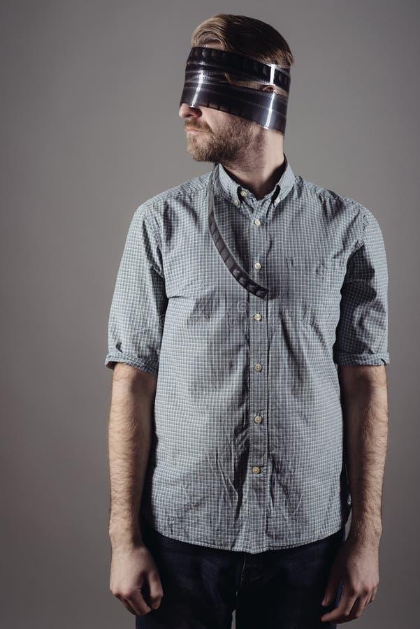 Hombre alegre un operador de cámara con un vendaje en su cabeza de una película imagenes de archivo