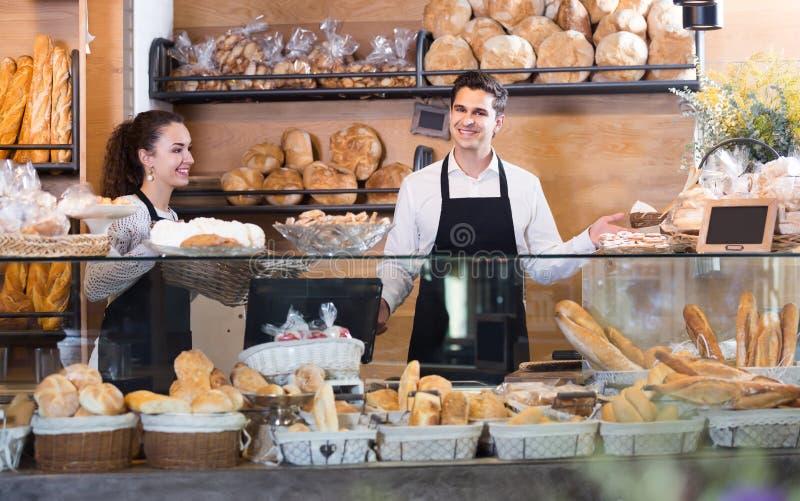 Hombre alegre y muchacha que venden los pasteles y los panes imagenes de archivo