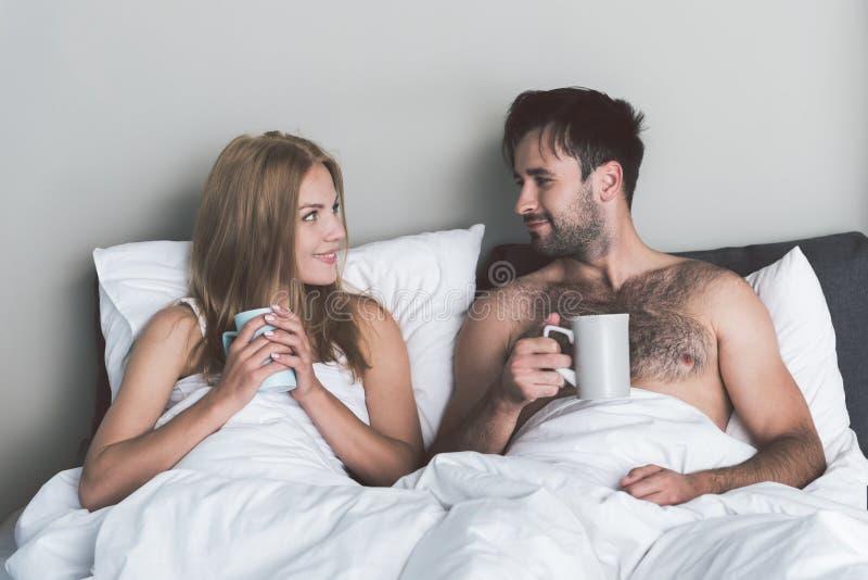 Download Hombre Alegre Y Mujer Que Disfrutan De La Bebida Caliente En Dormitorio Imagen de archivo - Imagen de cariñoso, calma: 100535071