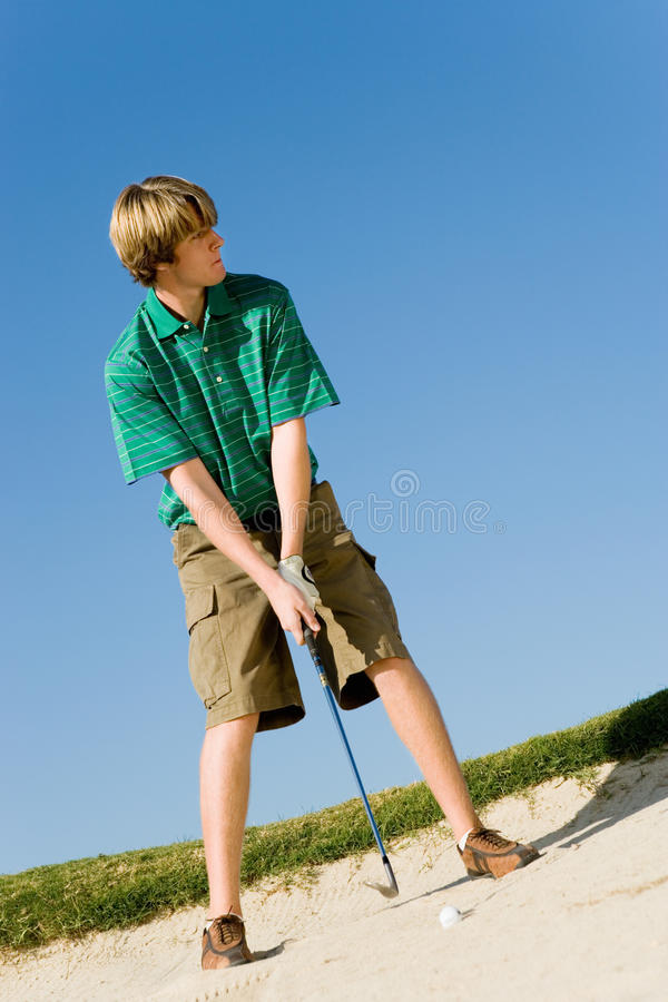 Hombre alrededor para golpear la bola fuera de una arcón de la arena imagen de archivo