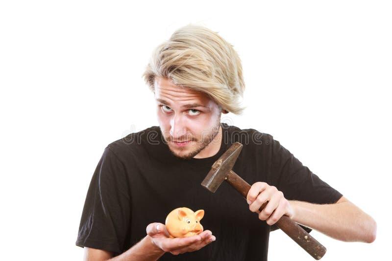Hombre alrededor para romper la hucha con el martillo foto de archivo libre de regalías
