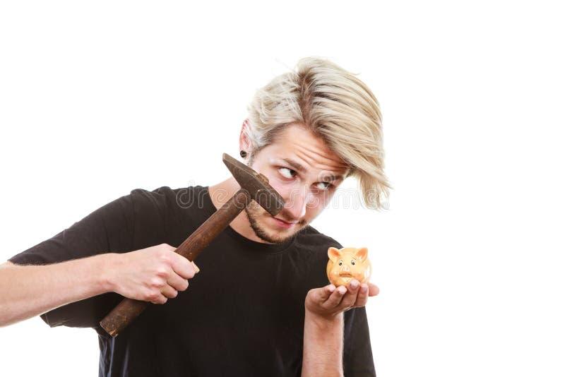 Hombre alrededor para romper la hucha con el martillo fotos de archivo