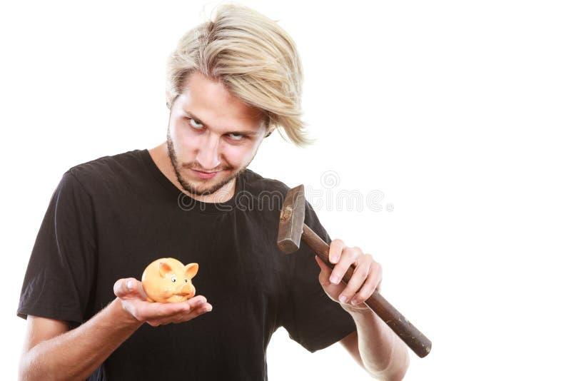 Hombre alrededor para romper la hucha con el martillo imágenes de archivo libres de regalías