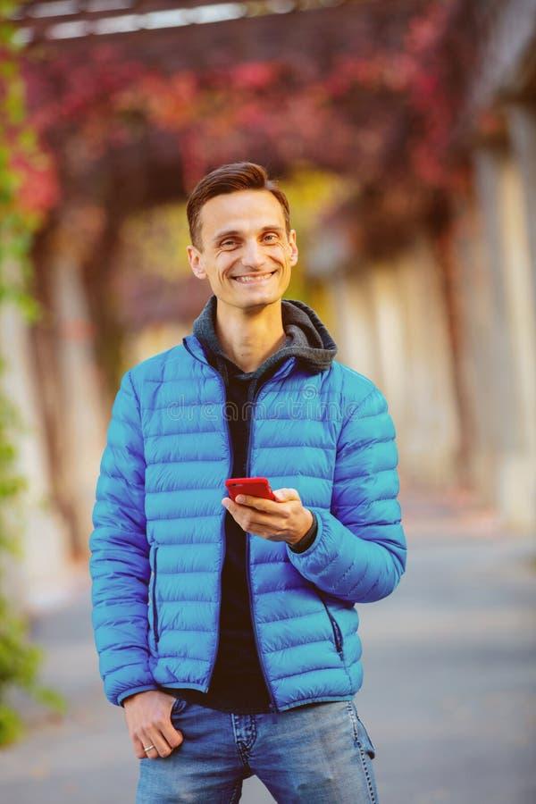 Hombre alto hermoso en chaqueta azul con el teléfono móvil fotografía de archivo