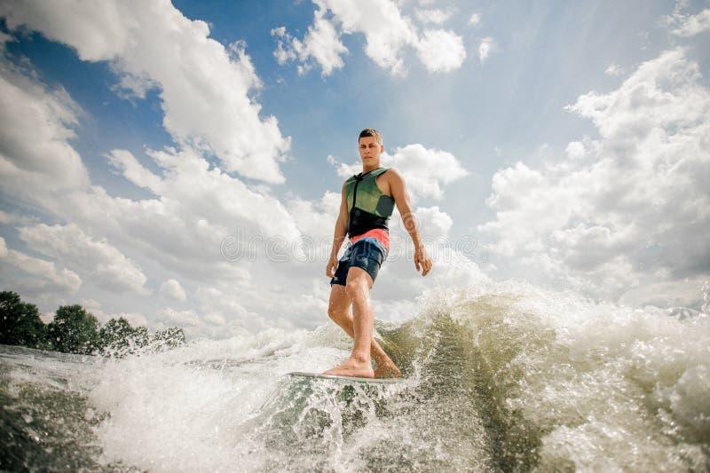 Hombre alto hermoso wakesurfing en el tablero rio abajo contra el cielo nublado y los árboles fotos de archivo libres de regalías