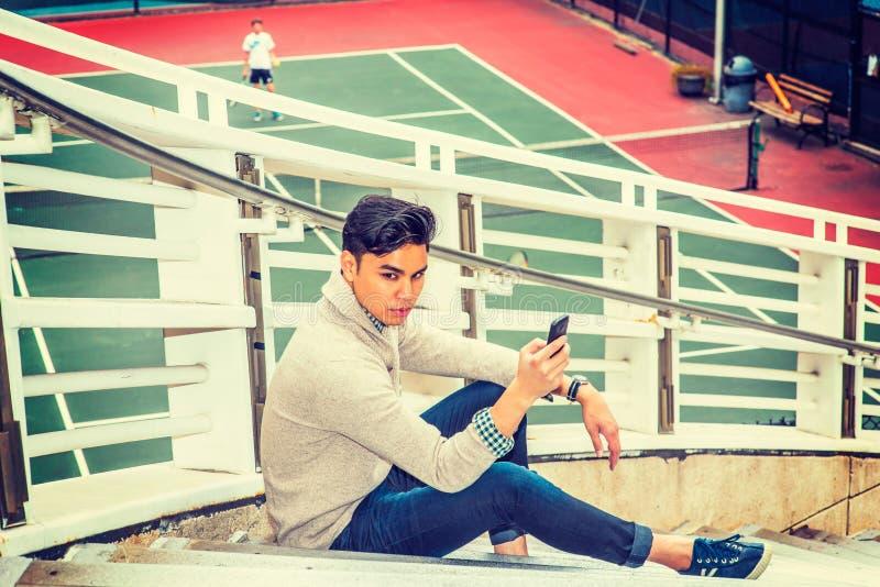 Hombre americano asiático joven que manda un SMS en el teléfono celular afuera en nuevo Yo imágenes de archivo libres de regalías
