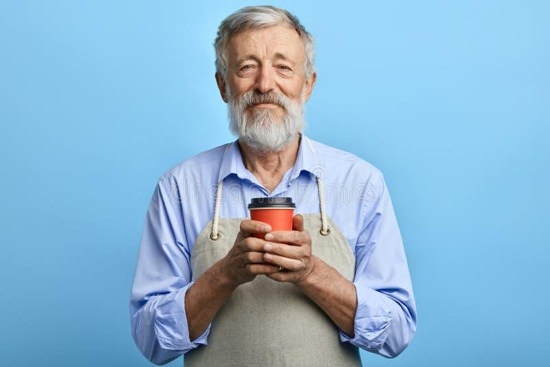 Hombre amistoso en el delantal gris que sostiene la taza disponible de bebida caliente imagen de archivo