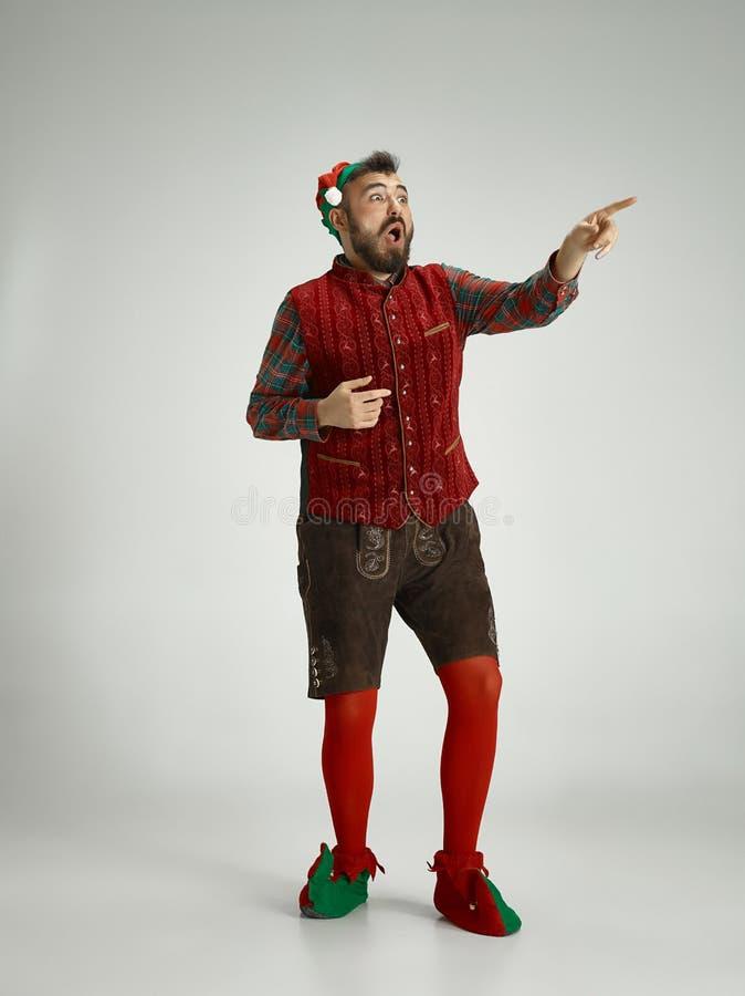 Hombre amistoso vestido como un gnomo divertido que presenta en un fondo gris fotos de archivo