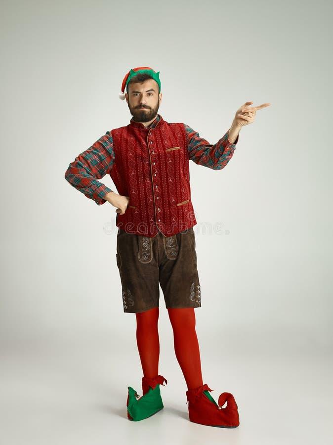Hombre amistoso vestido como un gnomo divertido que presenta en un fondo gris foto de archivo