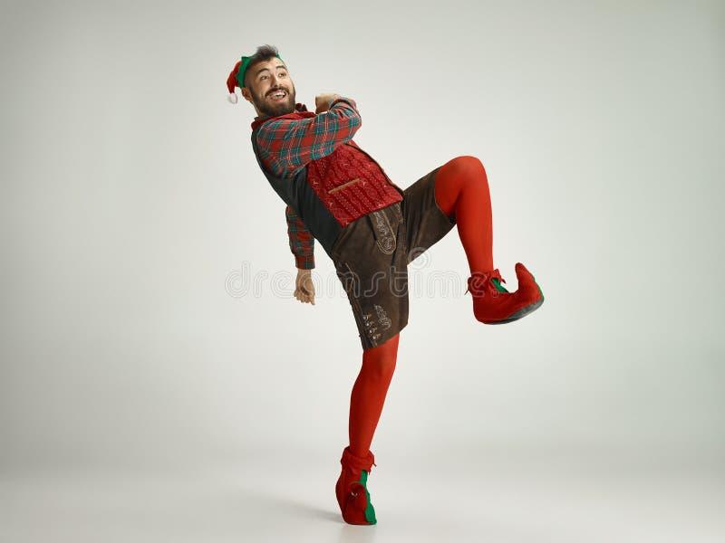 Hombre amistoso vestido como un gnomo divertido que presenta en un fondo gris foto de archivo libre de regalías