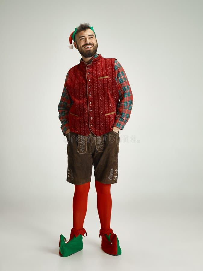 Hombre amistoso vestido como un gnomo divertido que presenta en un fondo gris imagen de archivo