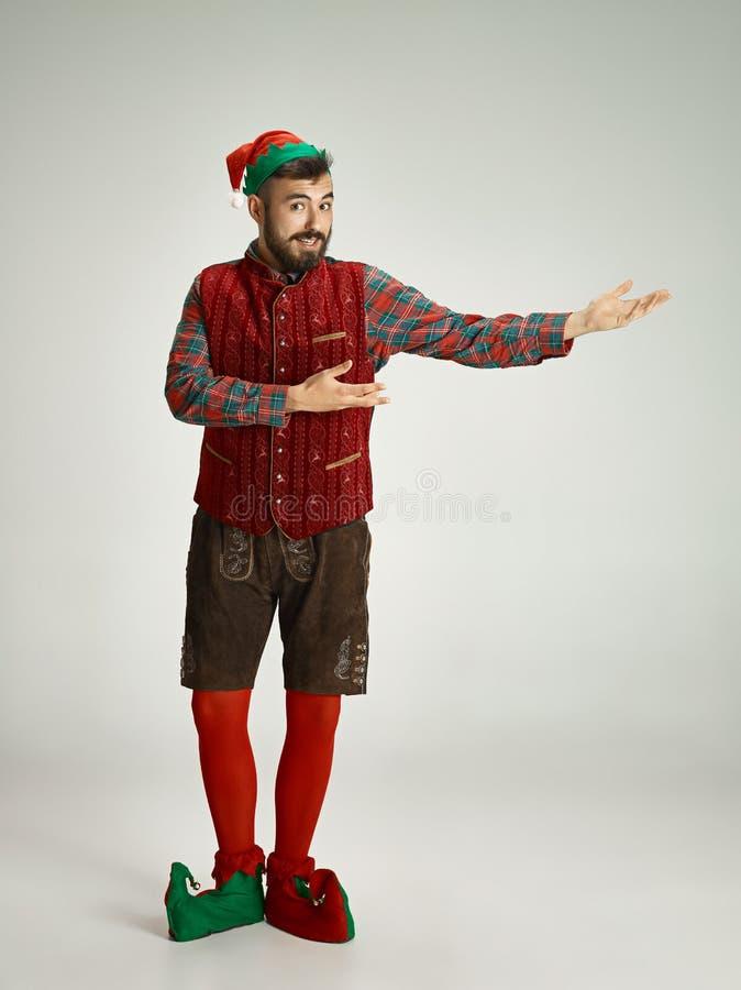 Hombre amistoso vestido como un gnomo divertido que presenta en un fondo gris aislado imagen de archivo libre de regalías