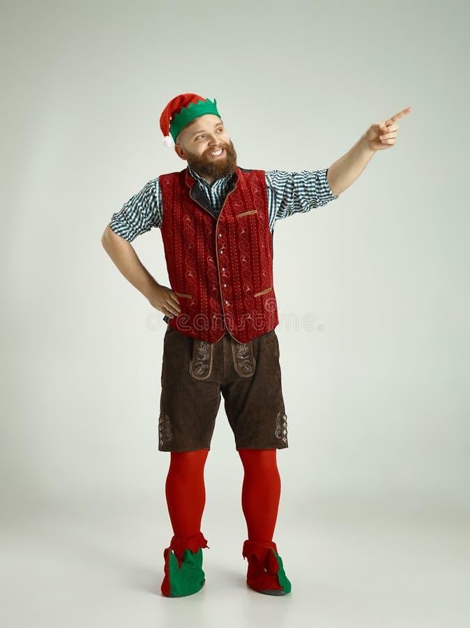 Hombre amistoso vestido como un gnomo divertido que presenta en un fondo gris aislado foto de archivo libre de regalías